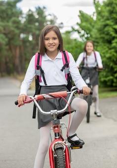 Zwei glückliche mädchen in schuluniform, die morgens auf fahrrädern fahren