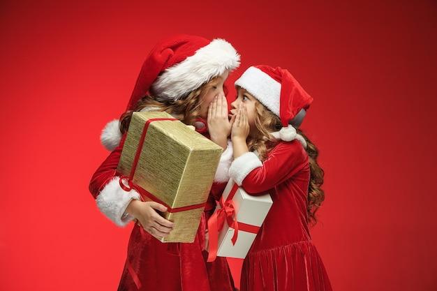Zwei glückliche mädchen in weihnachtsmannmützen mit geschenkboxen auf rot