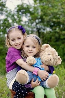 Zwei glückliche mädchen umarmen teddybär-spielzeug im freien