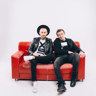 Zwei glückliche männer, die auf couch oder sofa sitzen und kamera lokalisiert auf weiß betrachten.