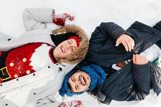 Zwei glückliche männer, die auf schnee liegen