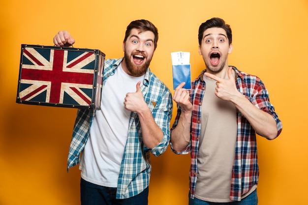 Zwei glückliche männer in hemden bereiten sich auf die reise vor, während sie sich über die gelbe wand freuen