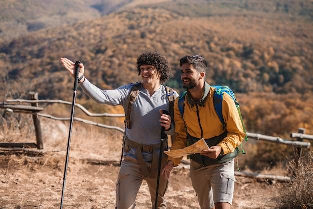 Zwei glückliche männliche freund, die im herbst wandern. einer von ihnen hält die karte, während der andere den richtigen weg zeigt. rucksäcke auf dem rücken.