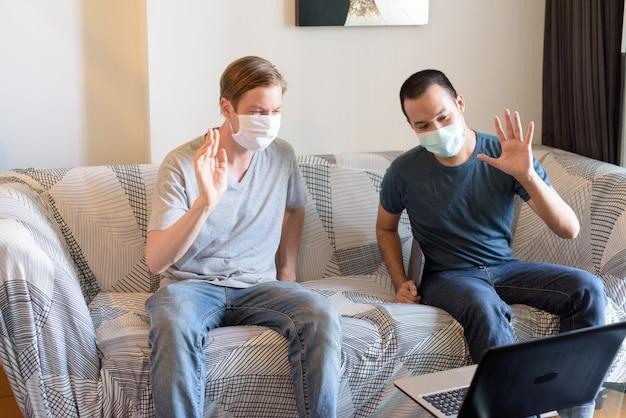 Zwei glückliche multiethnische männer mit maske als freunde videoanruf in quarantäne zu hause