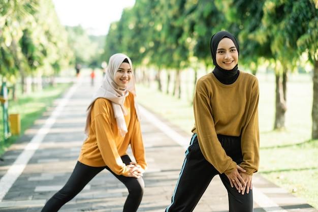 Zwei glückliche muslimische mädchen im kopftuch machen ausfallschritte, bevor sie joggen und sport treiben