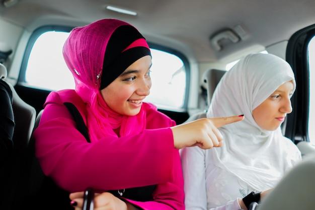 Zwei glückliche muslimische mädchen in einem auto, das in eine reise geht