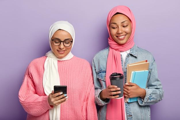 Zwei glückliche muslimische studenten machen eine kaffeepause