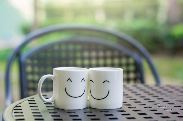 Zwei glückliche schalen auf der hölzernen tabelle, über liebeskonzept