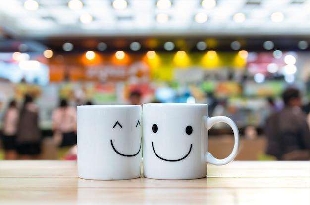 Zwei glückliche schalen auf kaffeespeicher-unschärfehintergrund