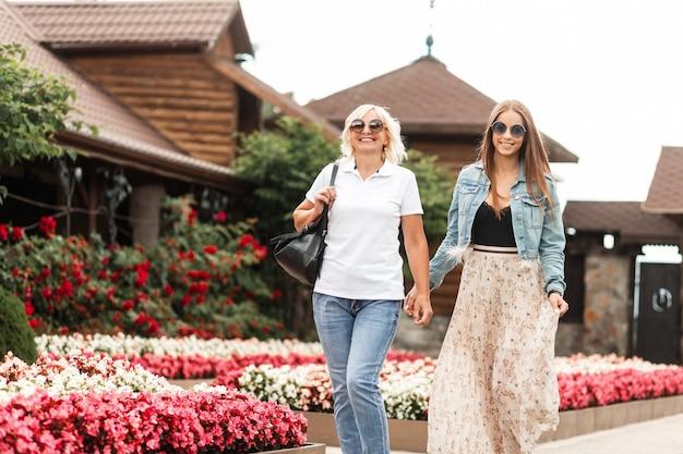 Zwei glückliche schöne frauenmama mit lächelnder tochter in modischer lässiger jeanskleidung gehen auf dem anwesen in der nähe von blumen