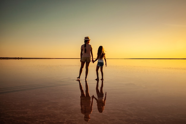 Zwei glückliche schöne schwestern gehen am spiegelsalzsee entlang und genießen den abendlichen feurigen sonnenuntergang