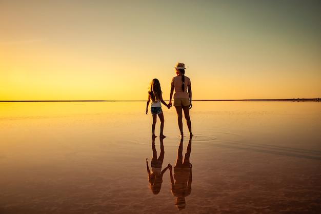 Zwei glückliche, schöne schwestern gehen am spiegelsalzsee entlang und genießen den feurigen sonnenuntergang am abend
