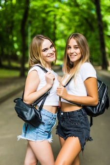 Zwei glückliche schüler, die im sommerpark gehen und sich unterhalten