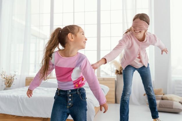 Zwei glückliche schwestern spielen zu hause mit verbundenen augen