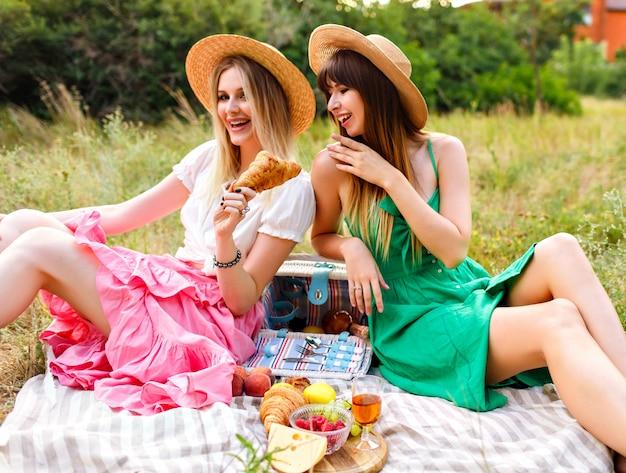 Zwei glückliche schwestern und beste freunde, die picknick im französischen vintage-stil genießen