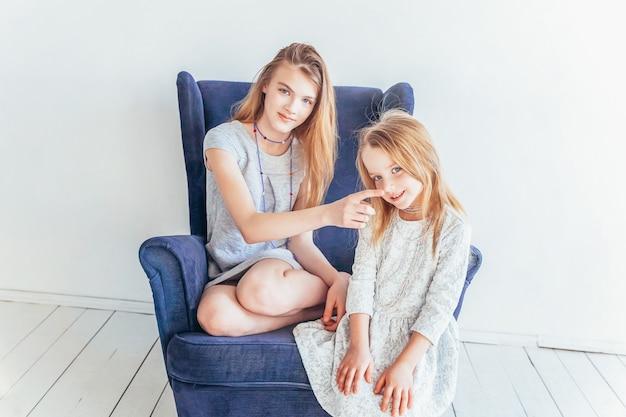 Zwei glückliche schwesternkinder, die auf gemütlichem stuhl sitzen und spaß zu hause haben