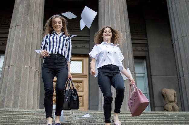Zwei glückliche studentinnen haben die prüfungen bestanden und gehen zur schule. sie rennen die treppe hinauf und werfen papiere gegen die universität weg