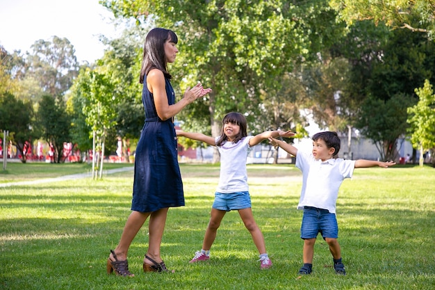 Zwei glückliche süße kinder und ihre mutter spielen aktive spiele im freien und machen übungen auf gras im park. familien-outdoor-aktivität und freizeitkonzept