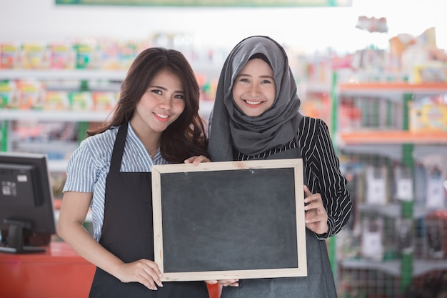 Zwei glückliche supermarktmitarbeiter mit leerer tafel