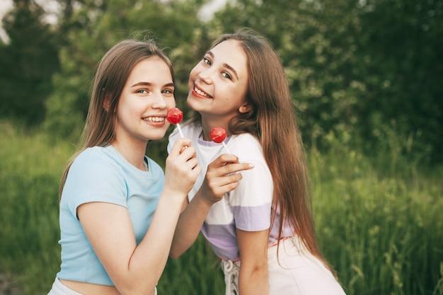 Zwei glückliche teenager-mädchen, die eine leuchtend rote lutschersüßigkeit halten