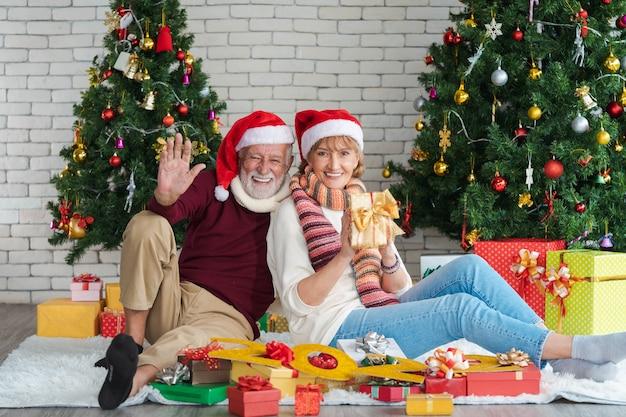 Zwei glückliche und fröhliche senioren mit weihnachtsmütze, die neujahr, neues leben und weihnachten zu hause feiern, die ein geschenk mit dekoriertem weihnachtsbaum im wohnzimmer mit der nummer 2022 halten. romantisches paar.
