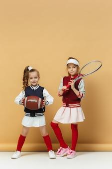 Zwei glückliche und schöne kinder zeigen unterschiedliche sportarten. emotionskonzept.