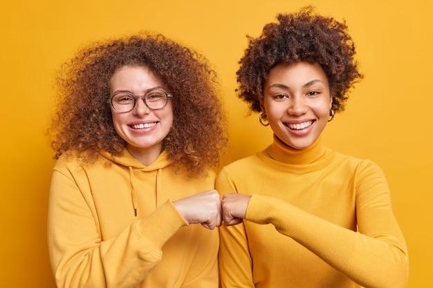 Zwei glückliche, vielfältige frauen machen faustschläge, die zustimmung zeigen, dass ein freundschaftliches beziehungslächeln glücklich nebeneinander steht, isoliert über gelber wand. teamwork körpersprache konzept