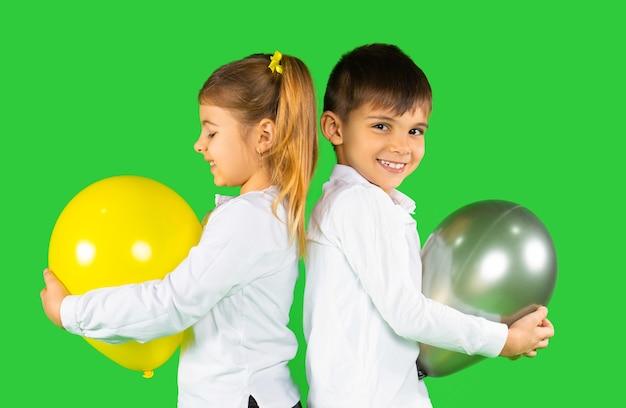 Zwei glückliche vorschulkinder mit luftballons auf einem leuchtenden und ultimativen grau