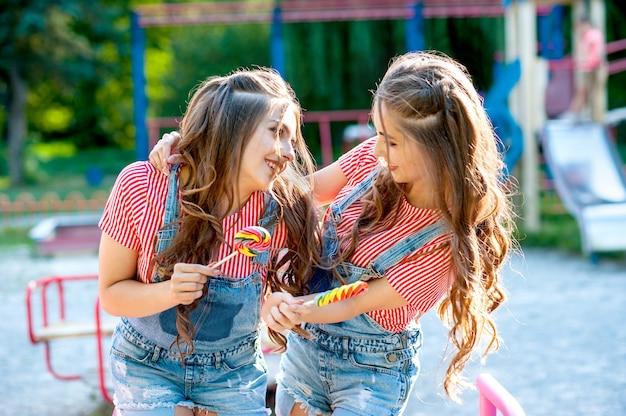 Zwei glückliche zwillingsschwestern, die in jeansoveralls mit lutschern auf dem spielplatz lachen