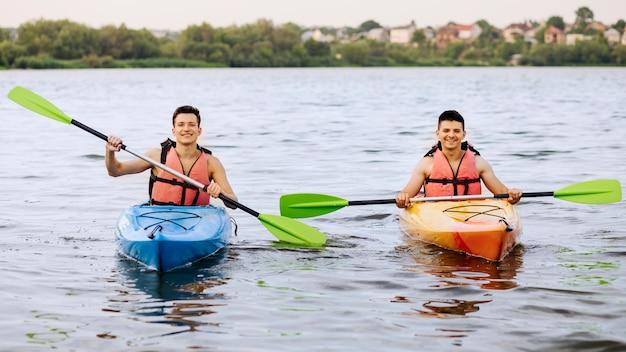 Zwei glücklicher mann, der auf see kayak fährt