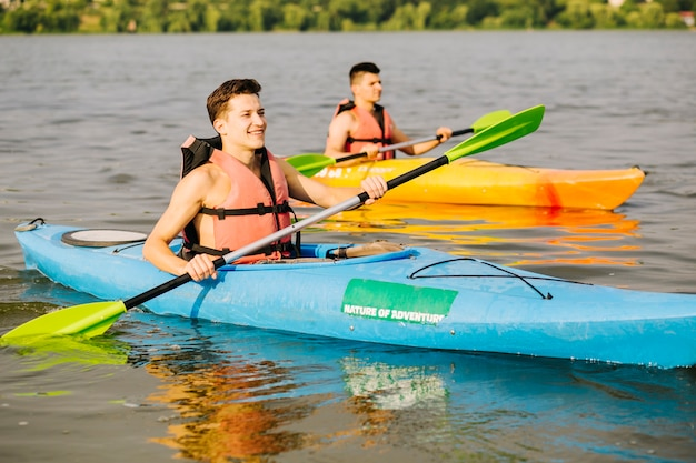 Zwei glückliches männliches kayak fahren auf fluss