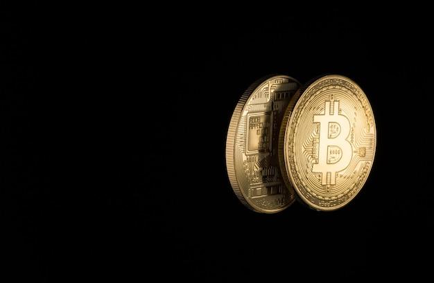 Zwei goldene bitcoins auf schwarzem hintergrund mit kopienraum. elektronisches geld isoliert