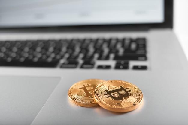 Zwei goldene bitcoins auf silberner laptoptastatur