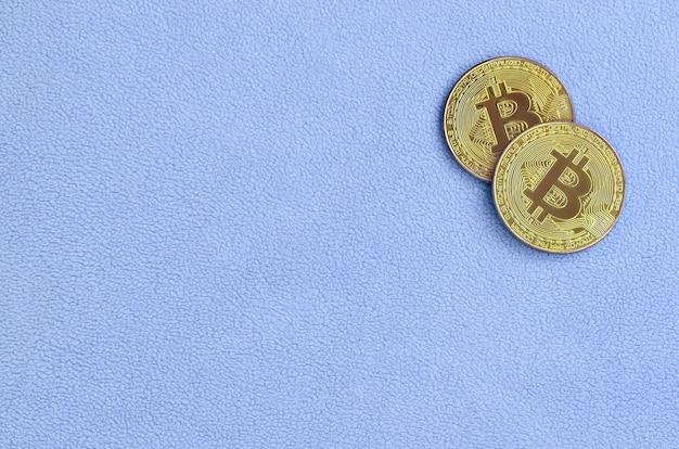 Zwei goldene bitcoins liegen auf einer decke aus weichem und flauschigem hellblauem fleece