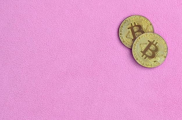 Zwei goldene bitcoins liegen auf einer decke aus weichem und flauschigem hellrosa fleece. physische visualisierung der virtuellen kryptowährung