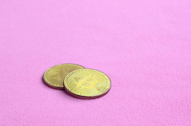 Zwei goldene bitcoins liegen auf einer decke aus weichem und flauschigem hellrosa fleece