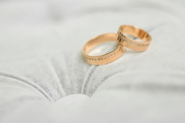 Zwei goldene eheringe auf grauem hintergrund