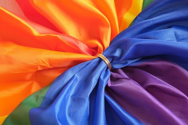 Zwei goldene eheringe auf regenbogen-lgbt-flagge. homosexuelle ehe. lgbt-rechte-konzept-kopierraum