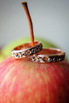 Zwei goldene eheringe auf rotem apfel, nahaufnahme. vintage ringe für braut und bräutigam, selektiver fokus. konzept der hochzeit
