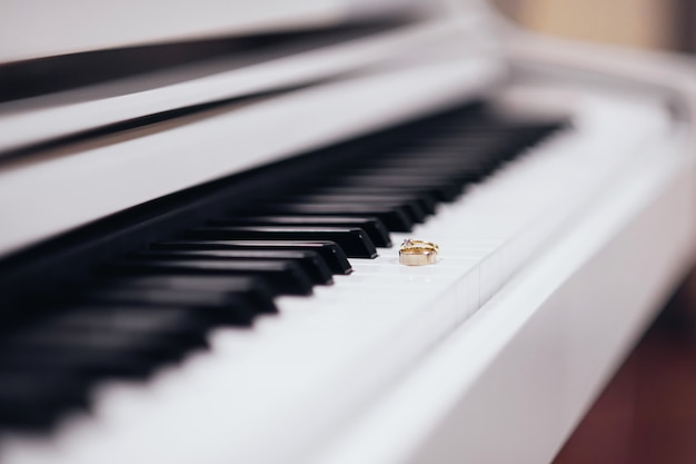 Zwei goldene eheringe, die auf den klaviertasten liegen