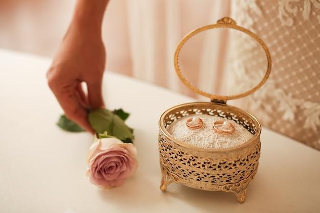 Zwei goldene eheringe in einer goldenen schachtel bei der hochzeit vor der ringverkleidungszeremonie.