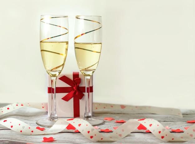 Zwei goldene gläser champagner mit einer geschenkbox und einem roten herzband