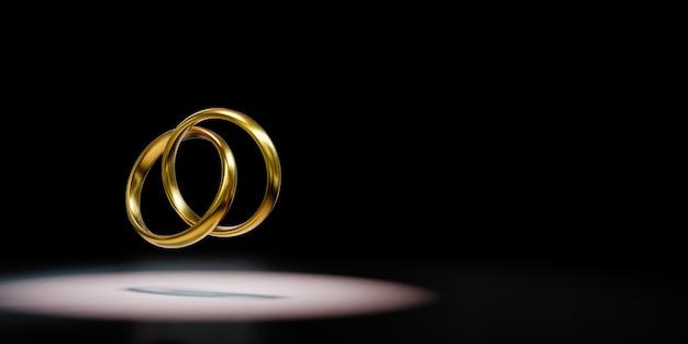 Zwei goldene ringe angekettet angestrahlt auf schwarzem hintergrund