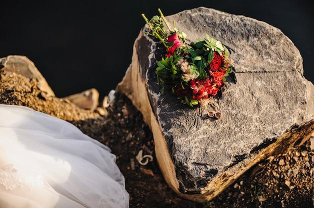 Zwei goldene ringe, die auf einem großen grauen stein neben blumenstrauß liegen
