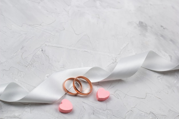 Zwei goldene ringe, rosa herzen und weißer satinbandhochzeitsdekor