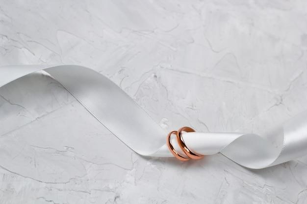 Zwei goldene ringe und weißer satinbandhochzeitsdekor oder hochzeitseinladungshintergrundkonzept