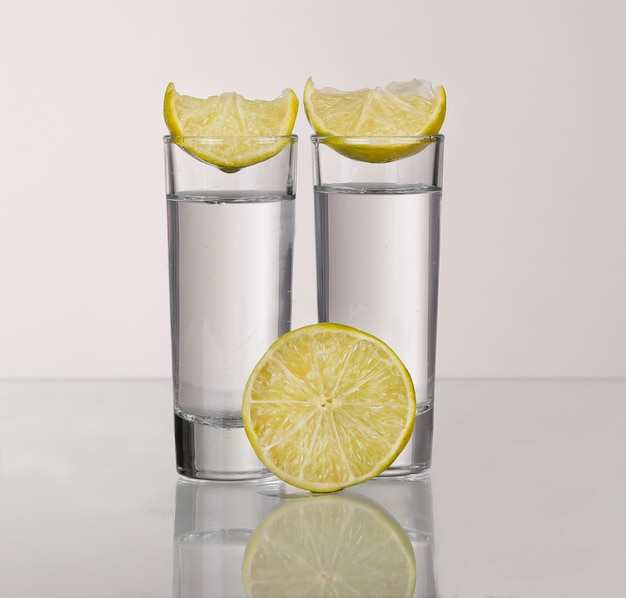 Zwei goldene tequila-schüsse mit kalk lokalisiert auf weißem hintergrund