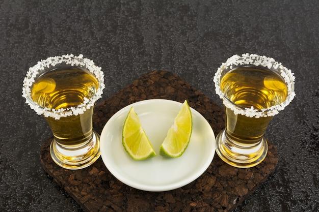Zwei goldene tequilaschüsse mit limette