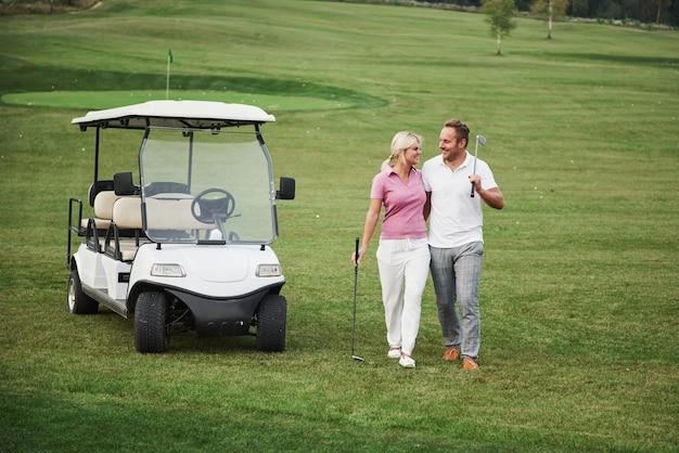 Zwei golfer, eine frau und ein mann, gehen gemeinsam zum nächsten loch. eine studentin geht mit ihrem personal trainer und freut sich über ihren sportlichen erfolg