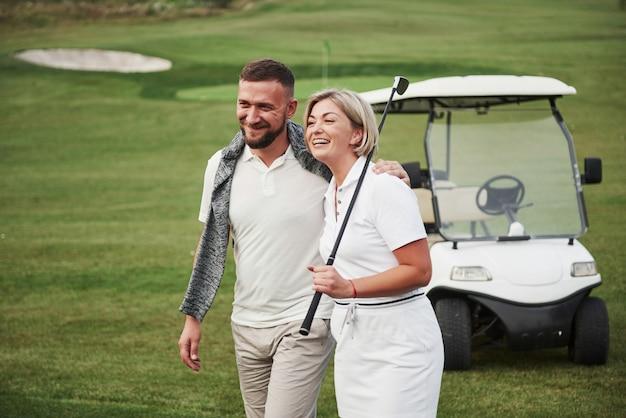 Zwei golfer, eine frau und ein mann, gehen zusammen zum nächsten loch. eine studentin geht mit ihrem personal trainer und freut sich über ihren sportlichen erfolg